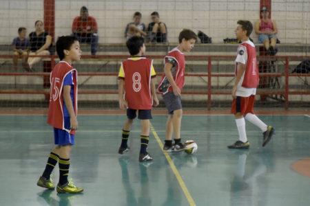 Quatro meninos com jaleco jogando futebol em quadra