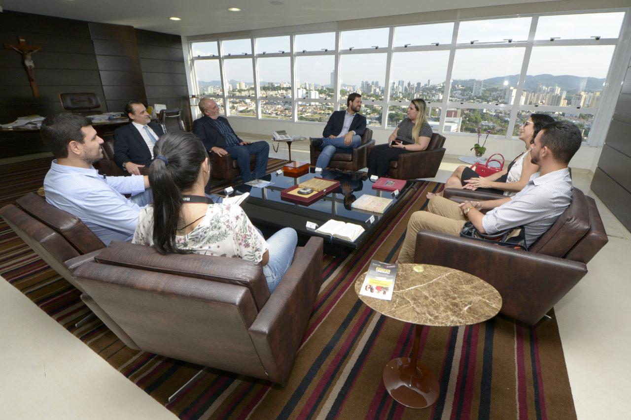 Pessoas sentadas em poltronas, em situação de reunião, com vista de panorama de cidade ao fundo