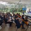 Pessoas sentadas em auditório, com pessoas sentadas, assistindo a uma apresentação de palestrantes sobre tablado elevado