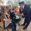 Homem fantasiado de chefe de estação ferroviária entregando passaportes em cesta para participantes da plateia
