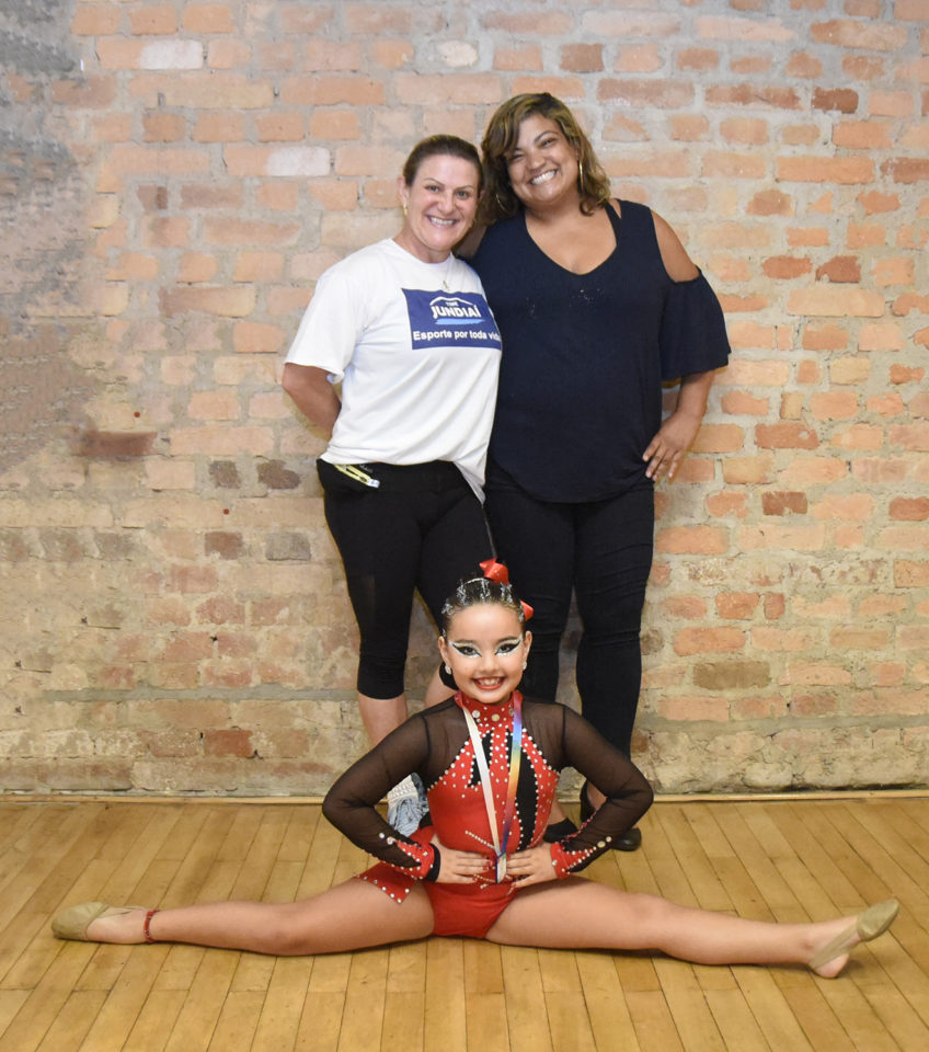 Mulheres em pé, em frente a parede de tijolos à vista, com menina à frente, com roupa de ginástica, com medalha no pescoço em pernas abertas em 180° como acrobacia