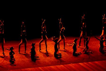 Atletas se apresentando em palco escuro, iluminado com luz vermelha