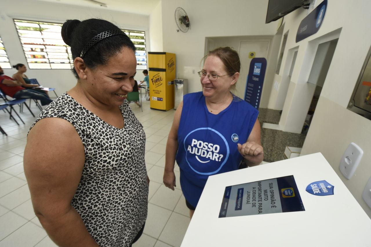 Duas mulheres, uma identificada por colete, auxilia a outra a mexer em um totem eletrônico