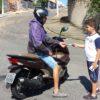 Motociclista recebe folder das mãos do aluno Davi Alves Silva