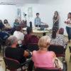 Pessoas sentadas em sala de aula, com pessoas em pé, falando, à frente da sala