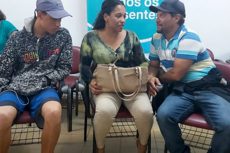 Três pessoas sentadas, conversando
