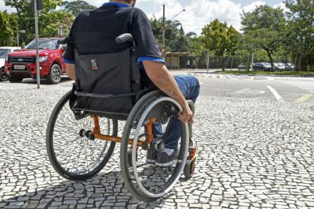 Foto sem identificação de cadeirante de costas em terreno plano