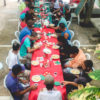 Foto de pessoas sentadas e almoçando ao redor de mesa comprida