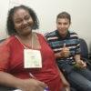 Mulher e rapaz jovens sentados, em foto posada, olhando para a câmera