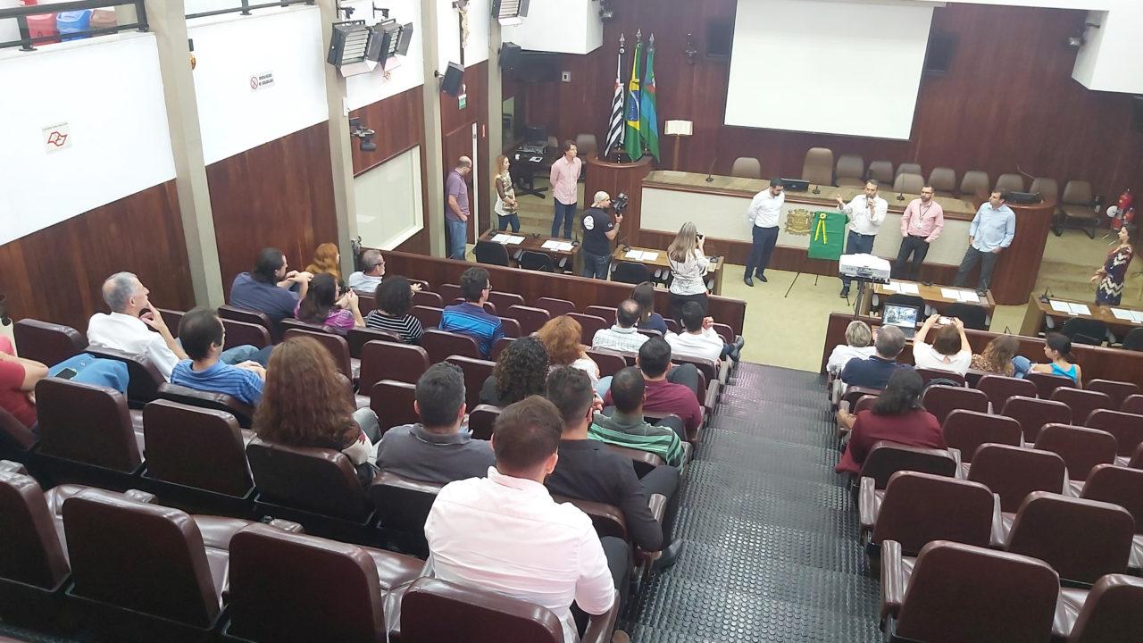 Plenária da Câmara Municipal, com pessoas sentadas e autoridades falando à frente