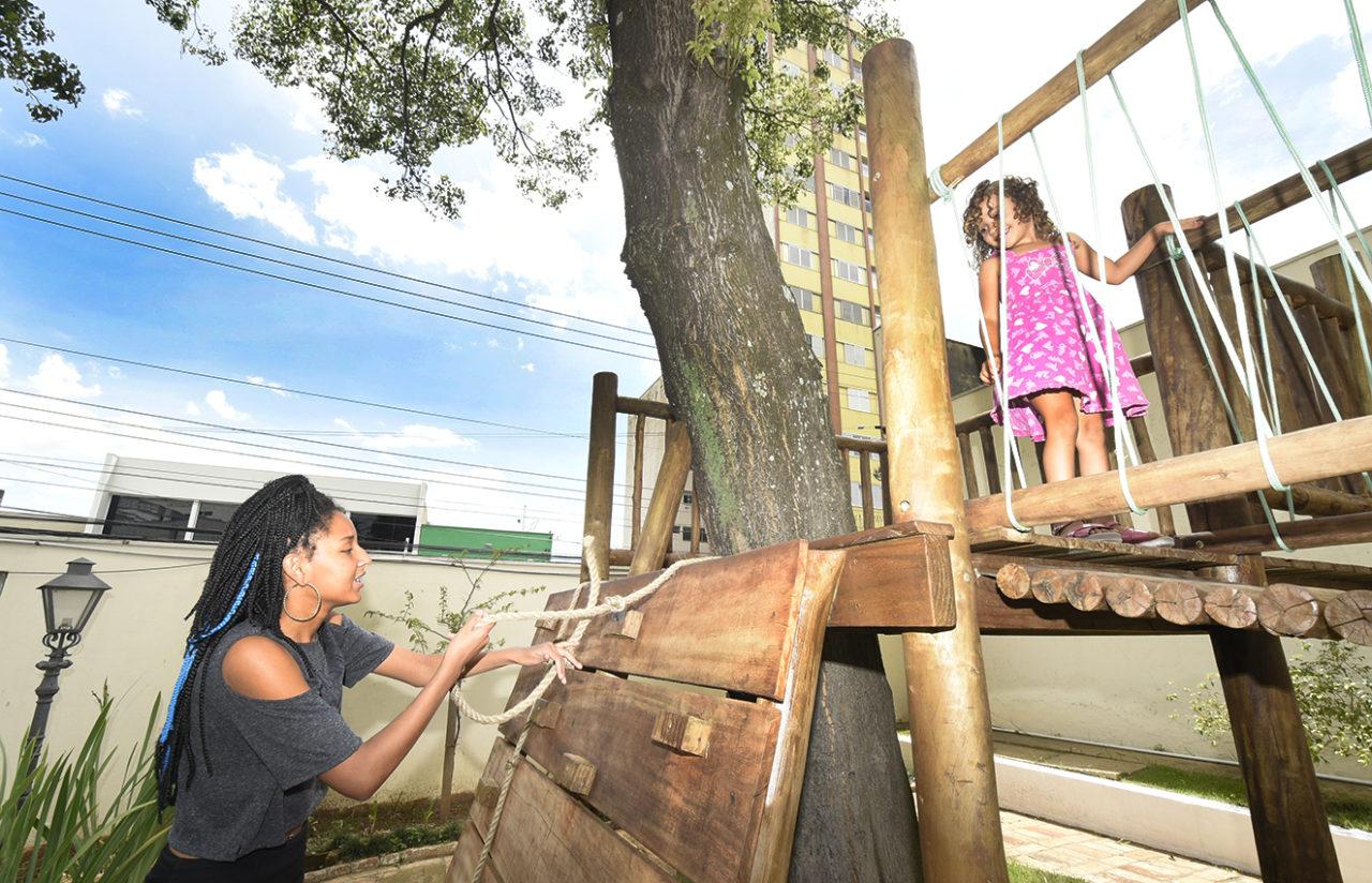 Mulher acompanha uma criança enquanto brinca em casa na árvore