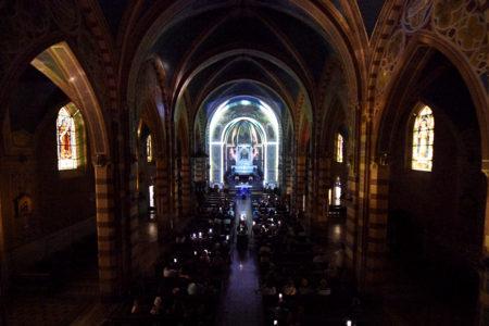 Interior de igreja no escuro, com projeções luminosas coloridas sobre as paredes