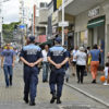 Dois guardasw caminhando em calçadão, com outros transeuntes passando