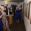 Pessoas olhando com atenção painéis na parede, com duas mulheres vestidas com roupa de época