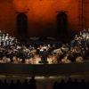 Palco de teatro, com músicos de orquestra e cantores de coral em arquibancadas montadas dos dois lados