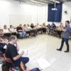 Sala de aula com cadeiras dispostas em semicírculo, com palestrante falando em pé à frente