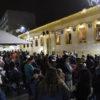 Fachada de prédio histórico iluminado com tema natalino e pessoas na rua de pedestre assistindo a uma apresentação de corais nas janelas