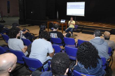 Auditório com pessoas de costas sentadas, com homem sentado á frente, falando no microfone, com telão ao fundo