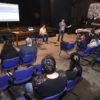 Pessoas sentadas em auditório, assistindo a uma apresentação de dois homens à frente, um sentado e outro em pé, com projetor de tela