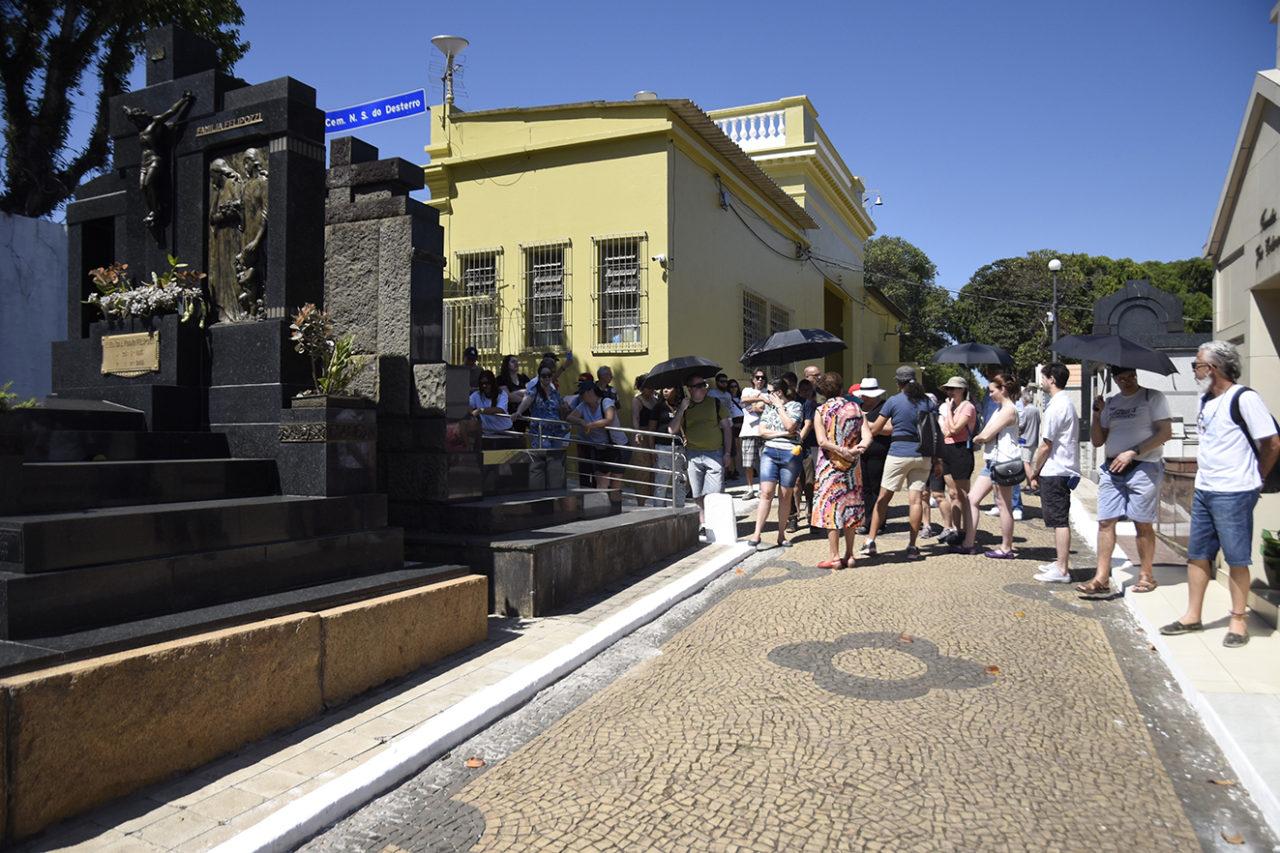 Túmulos de cemitério, com pessoas ao fundo em visita guiada