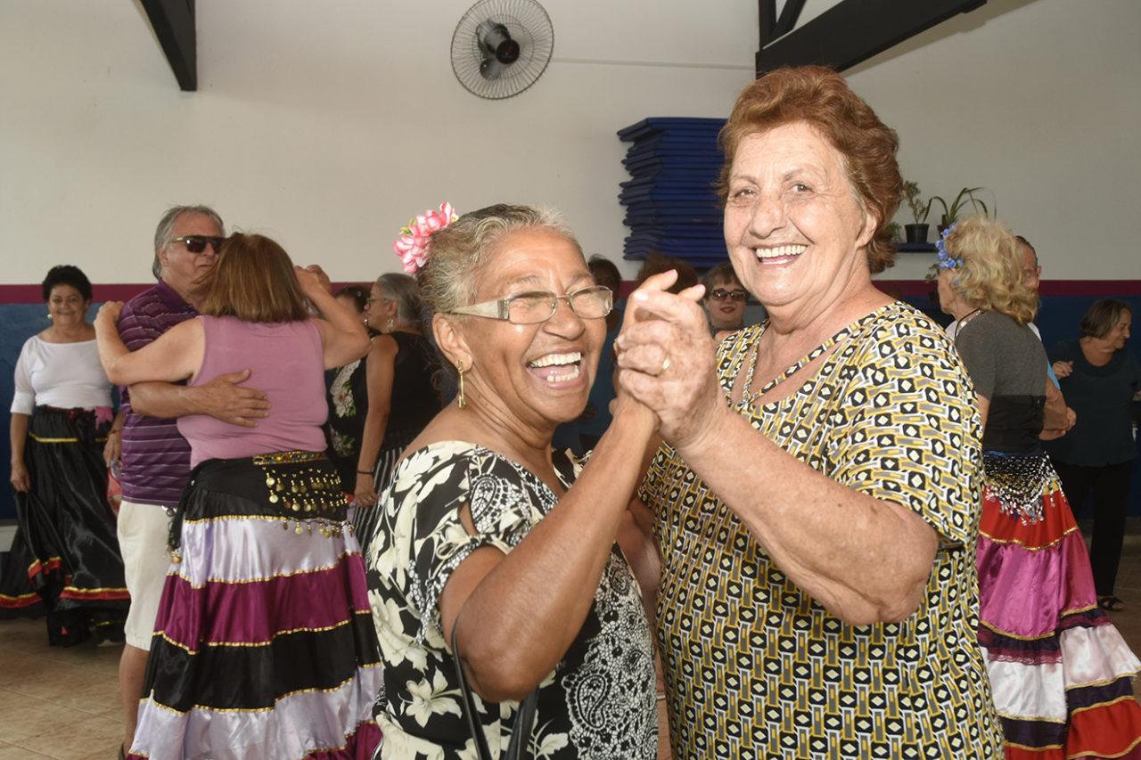 Duas mulheres idosas dançando, sorrindo
