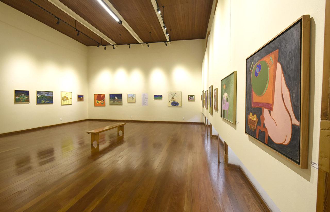 Espaço expositivo com quadros e obras de arte
