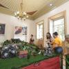 Maquete posicionada em centro de sala de prédio histórico, com visitantes