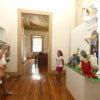 Criança posa pra foto em frente a presépio dentro de prédio histórico