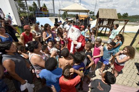 Homem fantasiado de Papai Noel interagindo com crianças em seu entorno