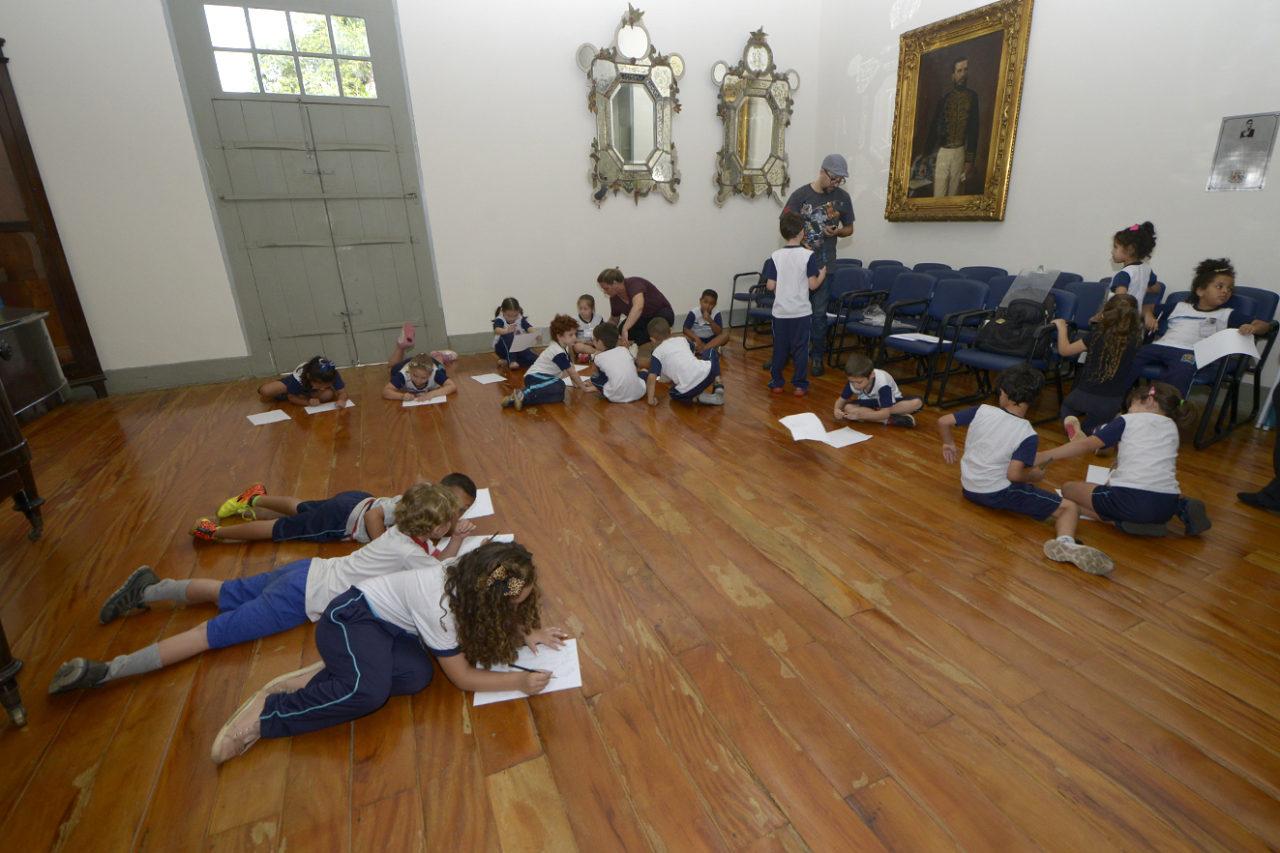 Salão de prédio histórico com crianças uniformizadas pintando em folhas de sulfite no chão