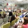 Sala de espera de hospital, com pessoas sentadas, assistindo a uma apresentação de músicos, usando gorros iguais ao do Papai Noel