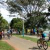 Parque com pessoas fazendo caminhada e andando de bicicleta