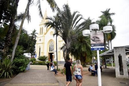 Praça com plantas e igreja ao fundo, com placa afixada em poste de iluminação