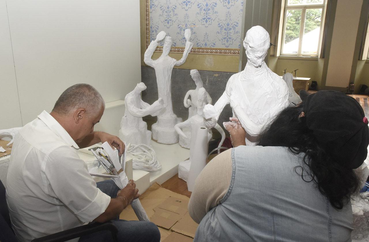 Pessoas de costas, sentadas, montando peças de artesanato em papel