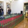 Maquete montada em meio a uma sala, com pessoas de costas, cantando para as janelas, e atores vestidos com roupas de época caminhando em corredor