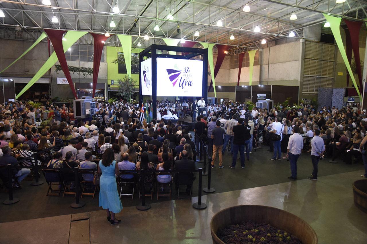 Galpão de eventos, com palco e pessoas sentadas na plateia