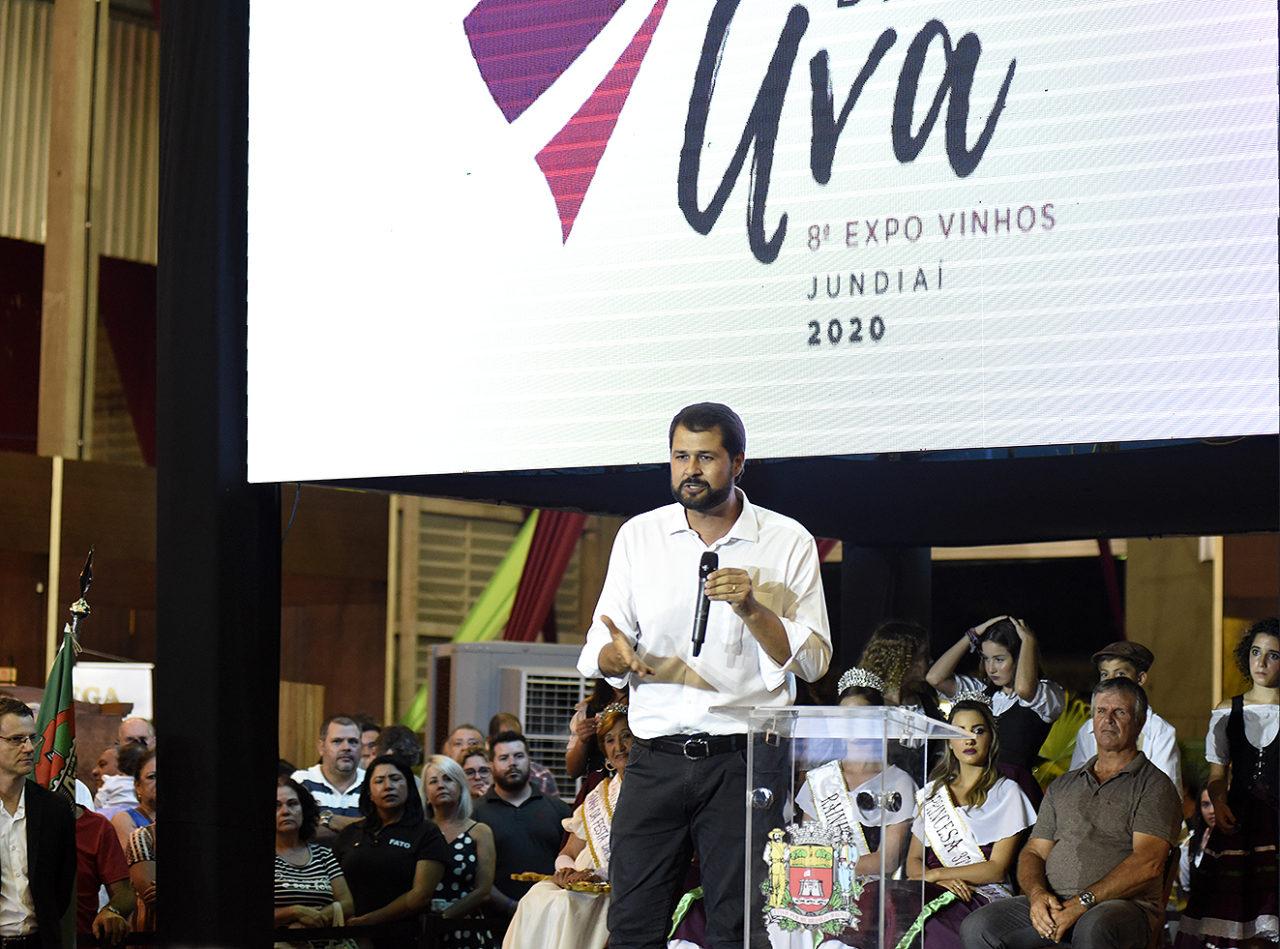 Homem falando ao microfone, com painel iluminado ao fundo