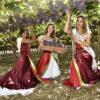 Três mulheres em traje de gala, em foto posada, sob parreiral de uvas Niagara Rosada