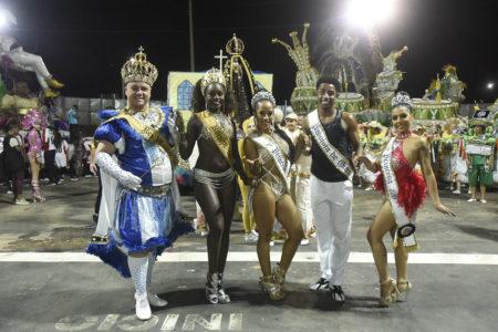 Personagens carnavalescos com fantasias, em foto posada em meio a uma avenida de desfiles