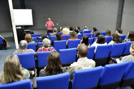 Auditórioc om pessoas sentadas, de costas, com palestrante falando à frente