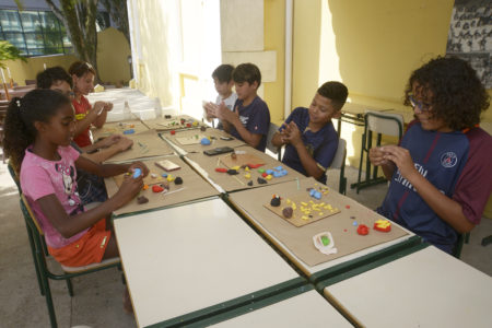 Crianças sentadas dos dois lados de mesas, brincando com massinha de modelar coloridas