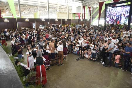 Galpão com multidão de pessoas e toneis de madeira com pessoas pisando uvas