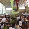 Pavilhão com multidão de pessoas e barracas de ambos os lados