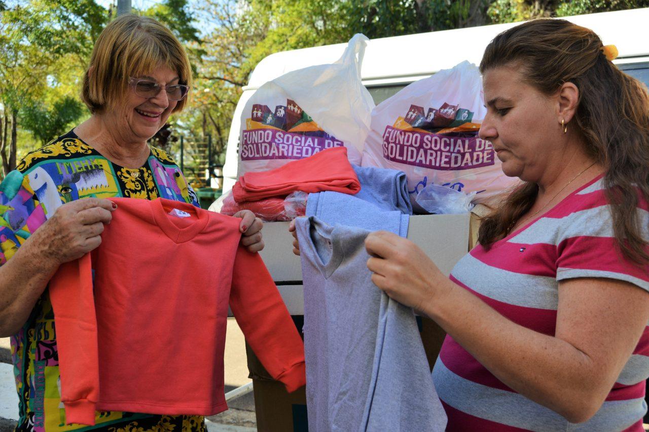 Voluntárias da entidade sorriem ao ver os agasalhos novos