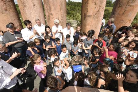 Crianças e adultos juntos, olhando para buraco onde menino posiciona um objeto com formato de foguete