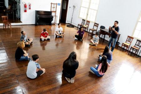 Crianças sentadas em formato circular em sala com assoalho de madeira