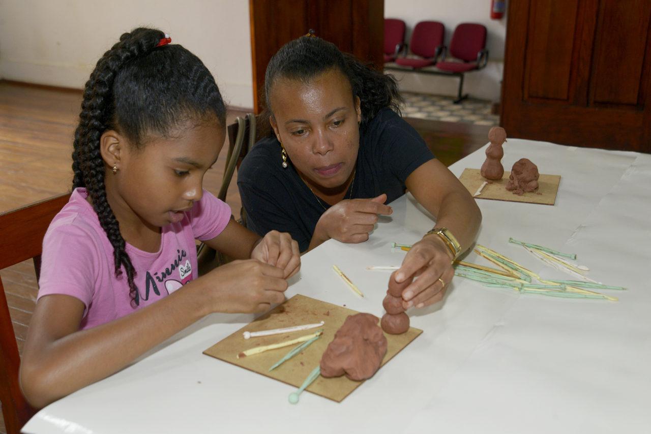 Mulher auxilia criança com material de modelagem