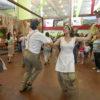 Pessoas com rioupas de imigrantes italianos, dançando em pavilhão