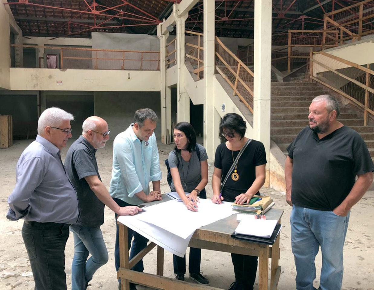 Saguão de edifício em obras, com pessoas ao redor de bancada, olhando para papeis com plantas arquitetônicas