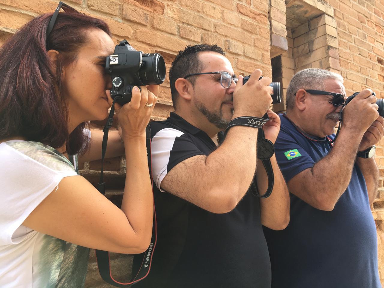 três fotógrafos apontando suas câmeras para o horizonte, alunos de um dos cursos da TVTEC.